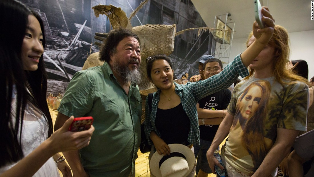 Artist Ai Weiwei looks at a fan's phone during his exhibition in Beijing on Saturday, June 6.