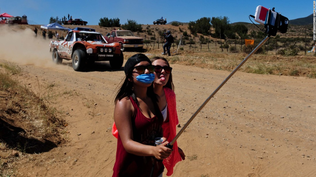 Young women use a selfie stick Saturday, June 6, during the Baja 500 race in Ojos Negros, Mexico.