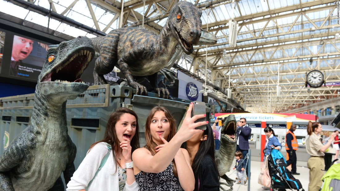 "People at a London train station take a selfie in front of a ""Jurassic World"" display on Monday, June 8. The film opens this week."