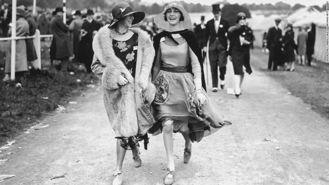 Two spectators wear floral dresses with wide-brimmed straw hats at Royal Ascot in the summer of 1928. Luxury clothing labels with connections to the worlds of horse racing and equestrian sport are reporting a resurgence of interest in classic styles.