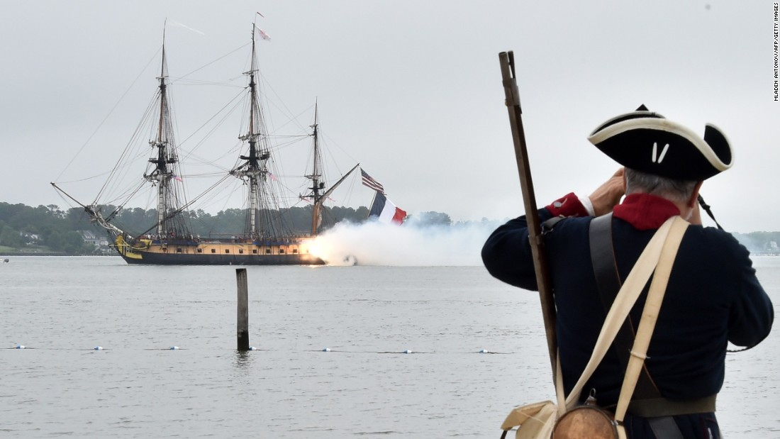 A man dressed in period costume watches as the vessel gives a 21 gun salute in the Yorktown City Harbor.