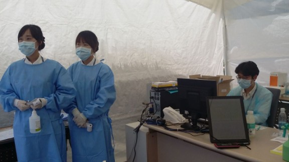 Health care workers wait for patients to treat at a tent outside a Seoul medical facility.