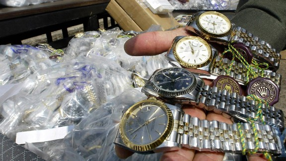 An unidentified Thai customs officer shows counterfeit Rolex watches confiscated in different raids during a display at the customs house in Bangkok, 11 March 2004. Thai authorities displayed different counterfeit items smuggled into the kingdom from overseas to show Thailand