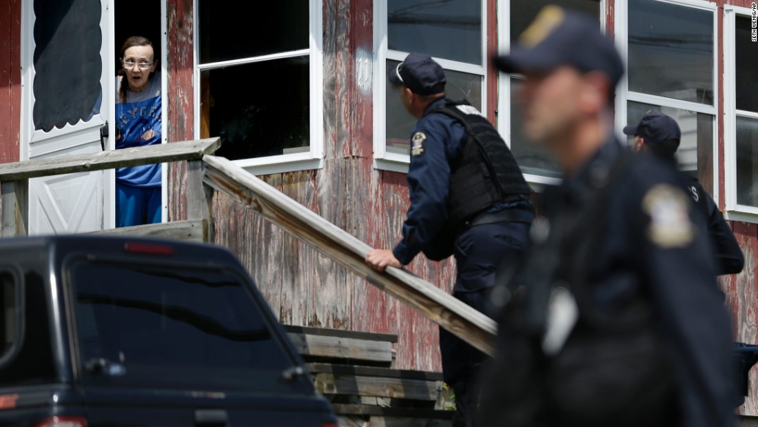 Law enforcement officers question a woman who lives near the Dannemora prison on Wednesday, June 10.