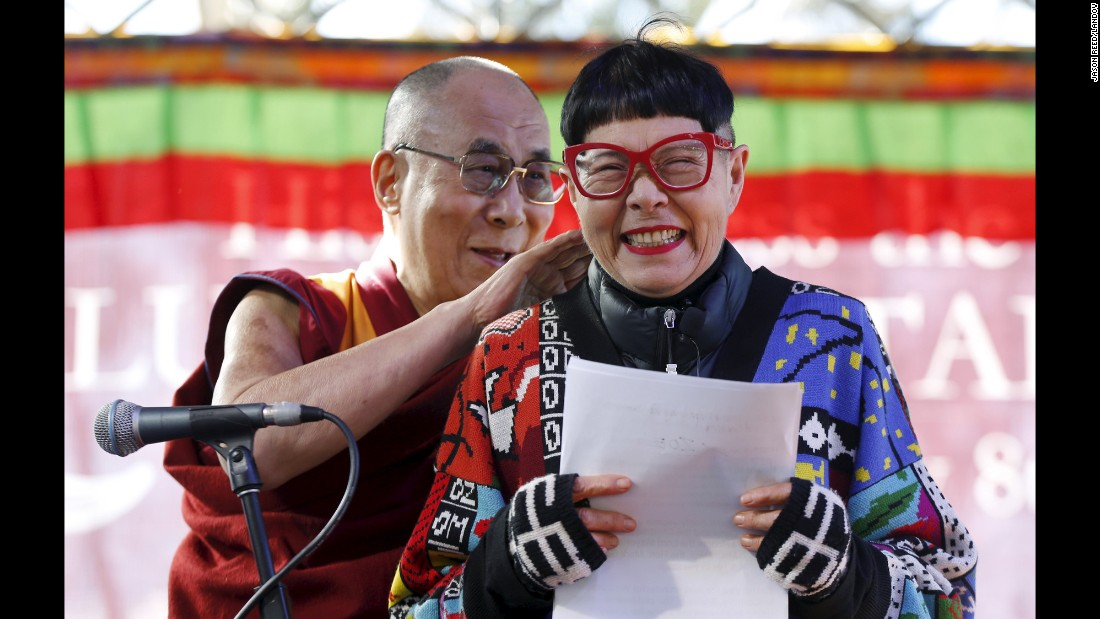A host reacts on stage as the Dalai Lama sneaks up behind her Monday, June 8, in Katoomba, Australia. It was the spiritual leader's first public appearance during his trip to the country.