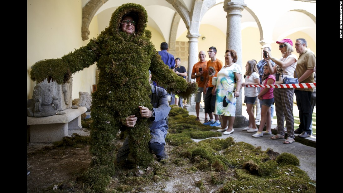 "Rosa Maria Diu is dressed as a ""moss man"" Sunday, June 7, inside a cloister in Bejar, Spain. It was part of an annual procession commemorating Christians who used moss as camouflage to hide from Muslim guards and re-conquer the town in the 12th century."