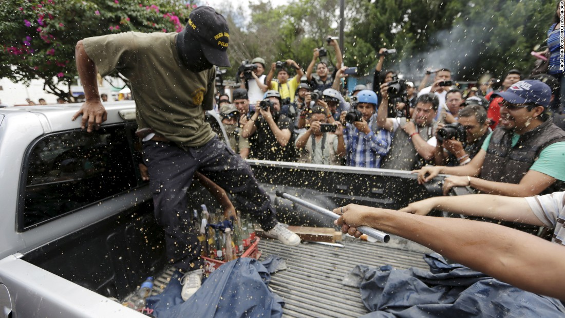 Soda droplets splatter as Tixtla villagers throw a bottle of Coca-Cola at a community policeman, whom they accuse of aiding a boycott of the elections, on a truck in Tixtla, in the state of Guerrero, Sunday, June 7.
