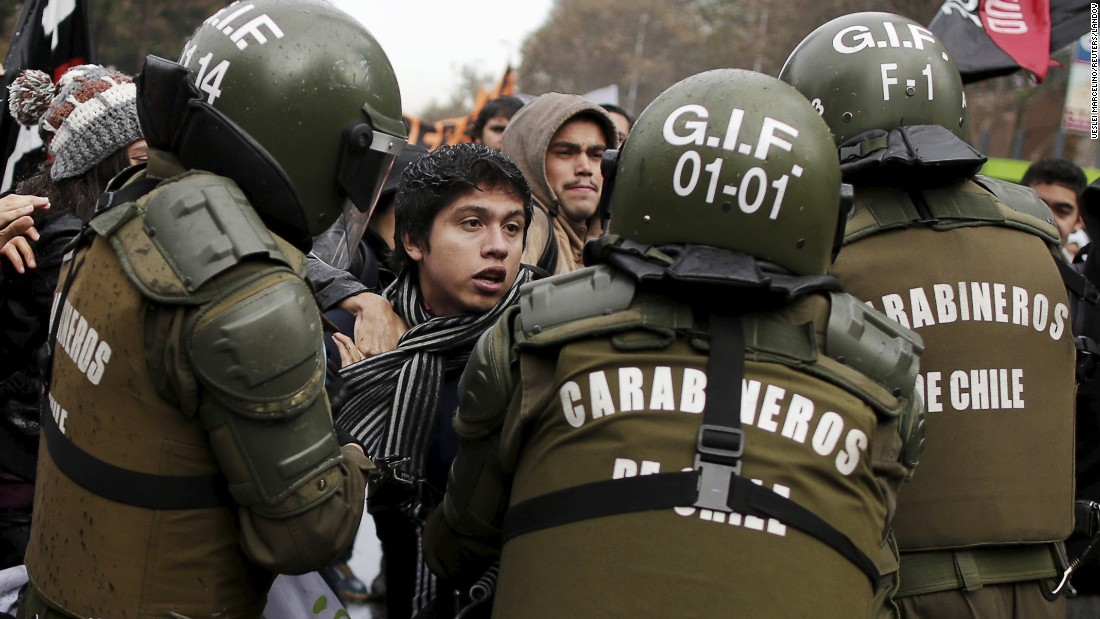 A protester in Santiago, Chile, is detained by riot police on Tuesday, June 9, during a demonstration demanding changes in the educational system.