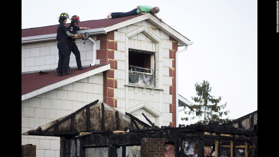 "Vadim Yaritsa checks his roof for damage next to the burned house where a police officer was shot and killed Tuesday, June 9, in Edmonton, Alberta. Constable Daniel Woodall, 35, was shot while serving a warrant on suspect Norman Raddatz, and Raddatz's house burned down following the shootout with police. A body that was thought to be Raddatz's was found in the basement, according to the <a href=""http://www.edmontonjournal.com/Friends+Norman+Raddatz+mourn+loss+shocked+police+shooting/11124487/story.html#__federated=1"" target=""_blank"">Edmonton Journal.</a>"