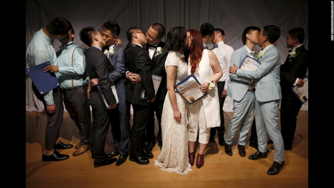Same-sex couples from China kiss after getting married at a group wedding in West Hollywood, California, on Tuesday, June 9. China does not recognize same-sex marriages.