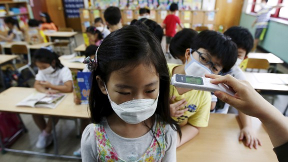 An elementary school student wearing a mask to prevent contracting MERS, receives a temperature check at an elementary school in Seoul, South Korea, on Tuesday, June 9.