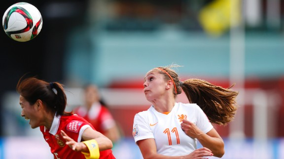 Wu Haiyan of China heads the ball in front of Lieke Martens of the Netherlands.