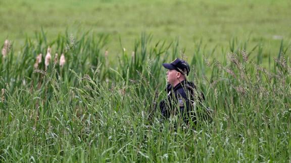 An officer walks through a swampy area near Essex on June 9.