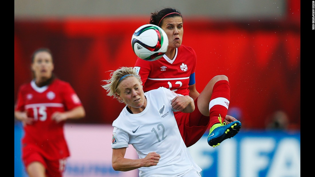 Christine Sinclair of Canada and Betsy Hassett of New Zealand battle for the ball.
