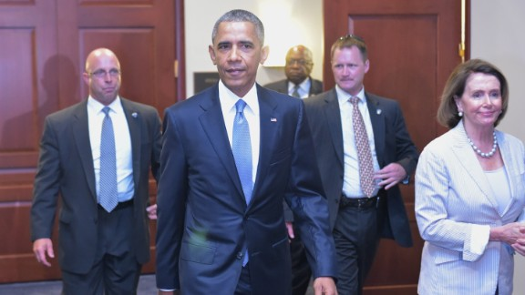 U.S. President Barack Obama and House Minority Leader Nancy Pelossi walk through a hallway after meeting on trade with House Democrats at the U.S. Capitol on June 12, 2015 in Washington, D.C.