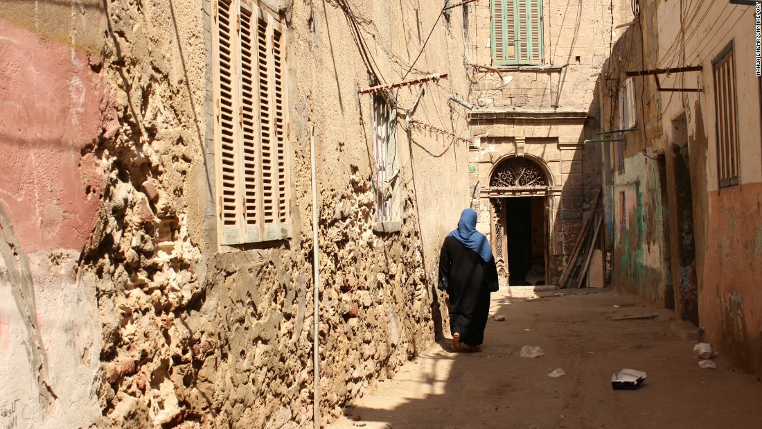 "<a href=""http://ireport.cnn.com/docs/DOC-1248211"">Nahla EINemr </a>shot this woman walking through Egyptian neighborhood Kom El Dikka. She felt that the photo represented Egypt in the architecture and traditional clothing shown. ""I love this photo because of the shadows cast on the woman's dress, like she is wearing those rays,"" EINemr said."