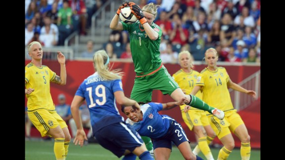 Swedish goalkeeper Hedvig Lindahl leaps over Leroux to catch the ball.