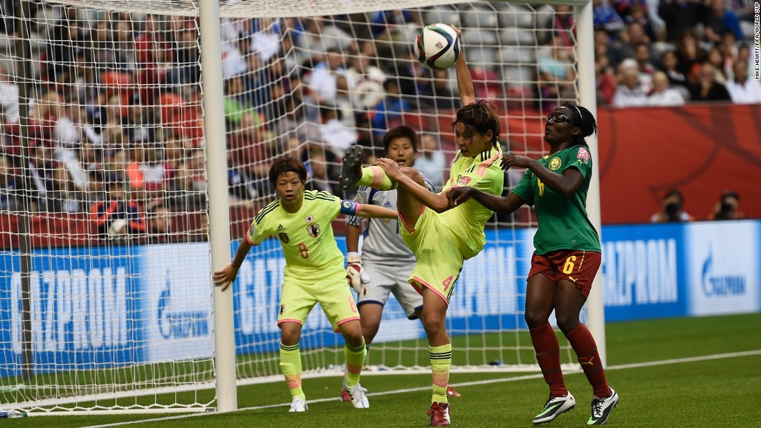 Saki Kumagai of Japan clears under pressure from Francine Zouga of Cameroon.