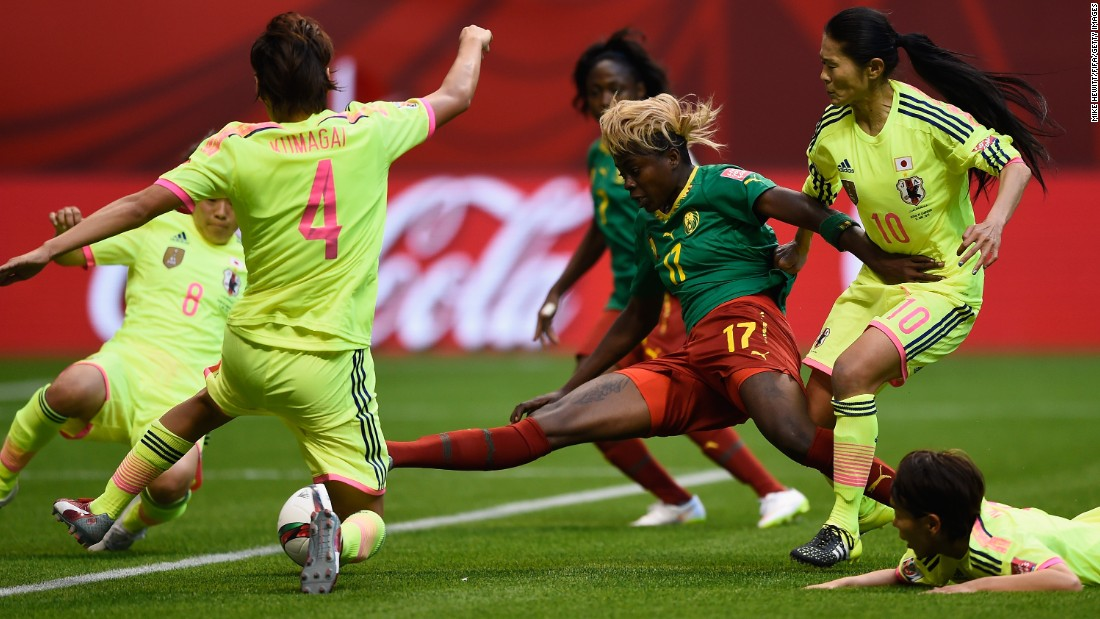 Cameroon's Gaelle Enganamouit is surrounded by Japanese defenders.