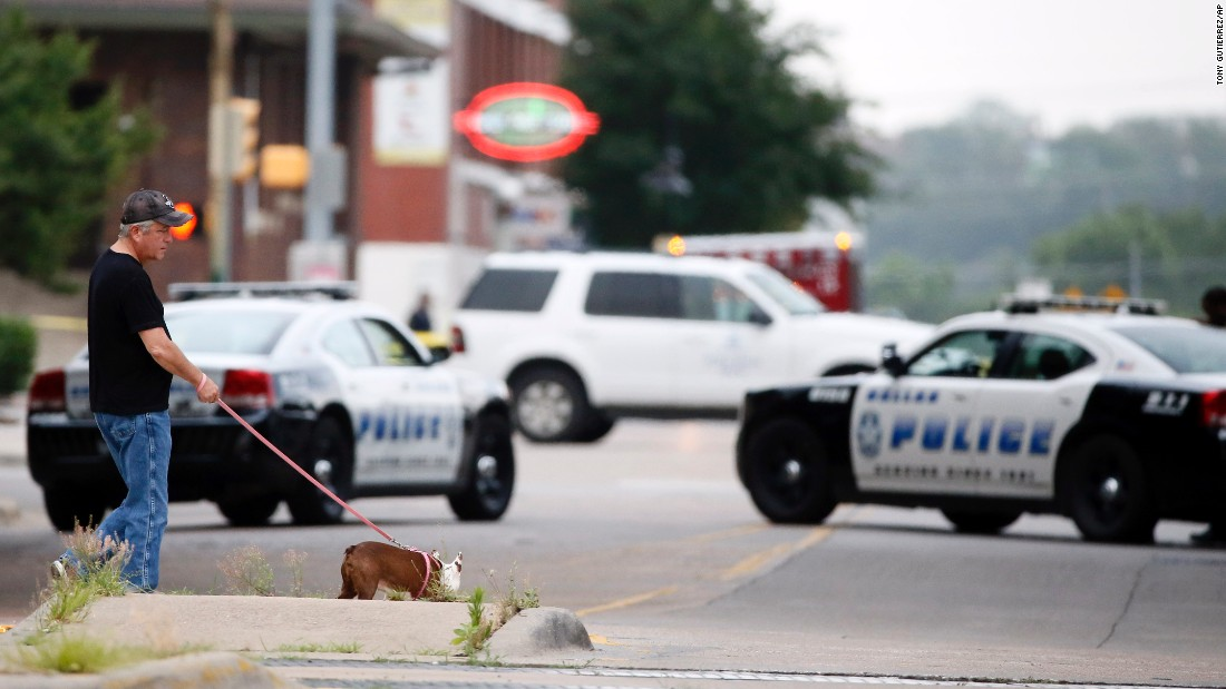 A resident walks his dog past police blocking the road near Dallas Police Department headquarters.