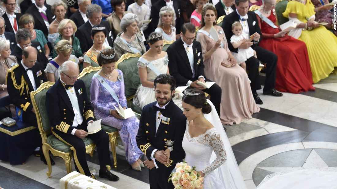 Prince Carl Philip Hellqvist stand at the altar during their wedding in the Royal Palace chapel. In the background are Sweden's King Carl Gustaf, Queen Silvia, Crown Princess Victoria, Prince Daniel and Princess Madeleine.