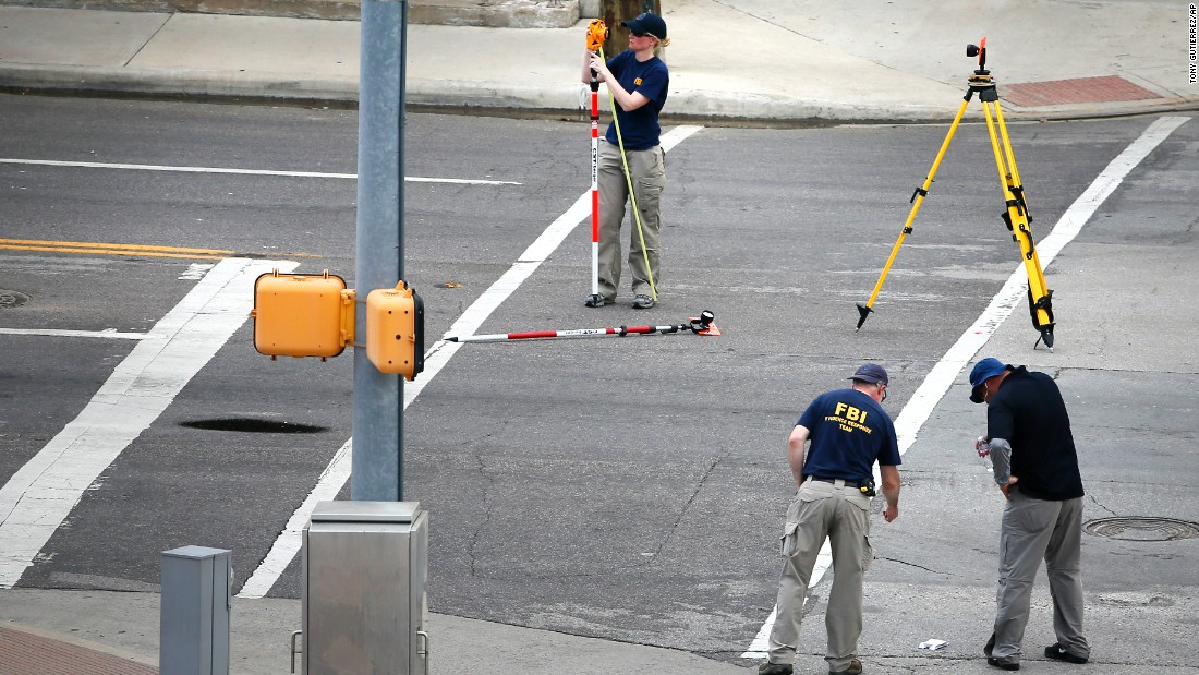 FBI evidence response team members look down at a piece of marked evidence on the street in front of Dallas police headquarters.