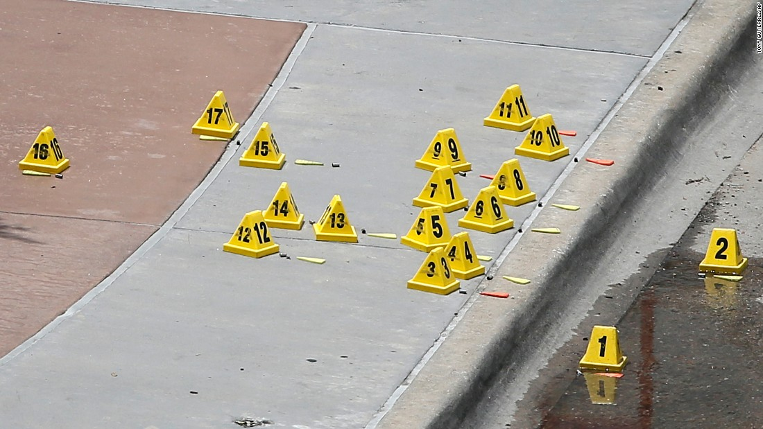 Evidence markers sit by bullet casings on a sidewalk near the police headquarters.
