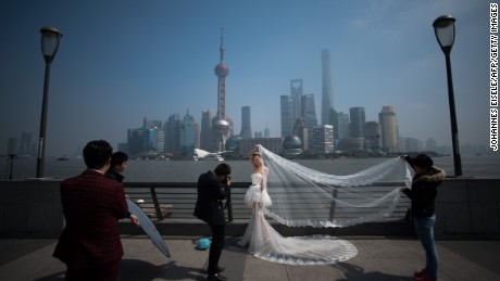 A woman poses for a wedding picture at the Bund in front of the financial district of Pudong in Shanghai on a sunny day on March 19, 2015.