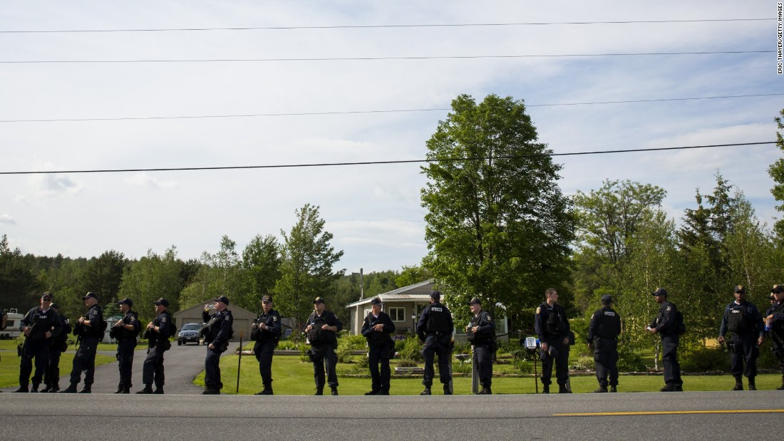 Law enforcement personnel line the roadside on June 13 as they search an area in Cadyville, New York.