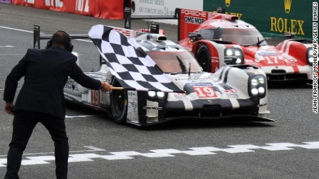 A race marshall waves the end of race black and white checkered flag as Germany's Nico Hulkenberg in his Porsche 919 - Hybrid N°19 (C) crosses the finish line to win the 83rd Le Mans 24 Hours endurance race, ahead of New Zealand's Brendon Hartley in his Porsche 919 -Hybrid N°17, on June 14, 2015 in Le Mans, western France. AFP PHOTO / JEAN-FRANCOIS MONIER (Photo credit should read JEAN-FRANCOIS MONIER/AFP/Getty Images)