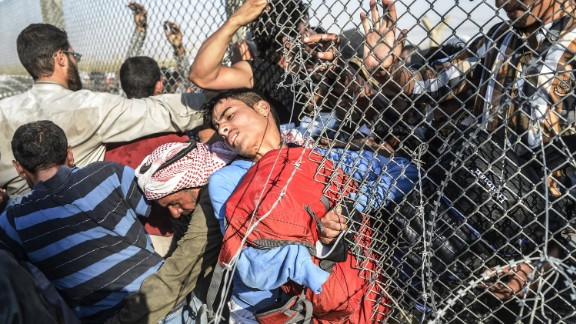 People force their way through a hole in the fence.