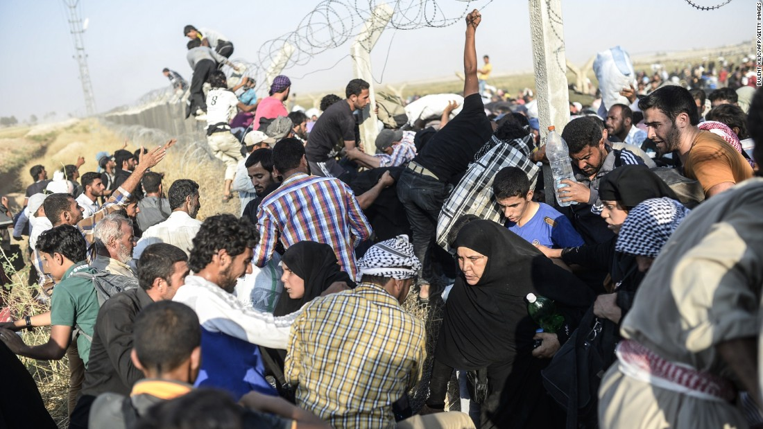 A crowd presses together as they struggle to cross through and over the broken border fence. The flow of refugees increased as Kurdish fighters closed in on the ISIS-held town of Tal Abyad, on the opposite side of the border to Akcakale.