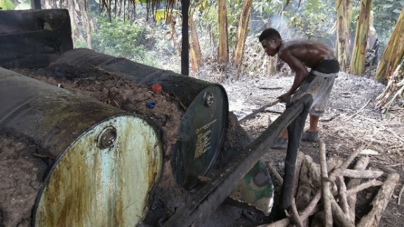 A  young man puts more wood on the fire to heat drums of fermented palm sap and evaporate the alcohol.