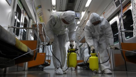 Disinfection workers wearing protective gears spray anti-septic solution in an subway amid rising public concerns over the spread of MERS virus at Seoul metro railway base on June 9, 2015 in Goyang, South Korea.