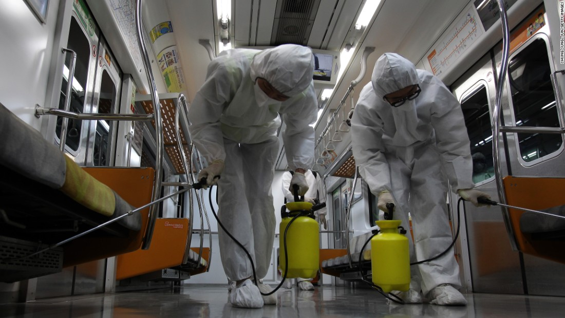 Disinfection workers wearing protective gears spray anti-septic solution in a subway amid rising public concerns over the spread of the MERS virus at Seoul metro railway base on June 9, 2015 in Goyang, South Korea.