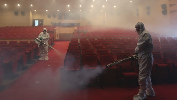 Workers wearing protective gears spray antiseptic solution as a precaution against the spread of MERS at an art hall in Seoul, South Korea, on Friday, June 12, 2015.
