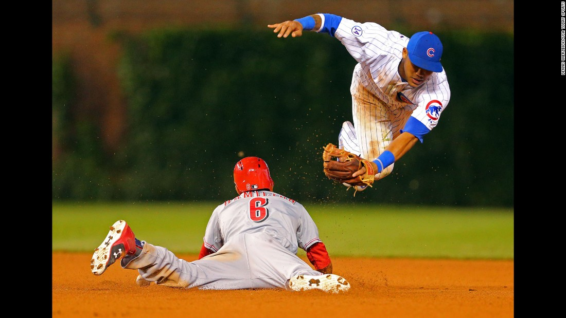 Cincinnati's Billy Hamilton steals second base, avoiding Addison Russell's tag Sunday, June 14, in Chicago. Hamilton had five stolen bases in the game, which Cincinnati won 2-1.