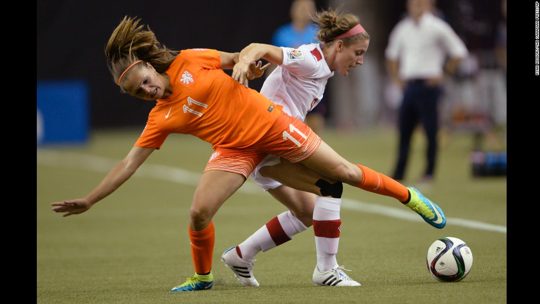 Lieke Martens of the Netherlands and Canada's Josee Belanger compete for the ball.