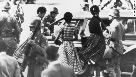 Black students are provided with a military escort when entering and leaving Little Rock Central High School, Arkansas, following the school's desegregation in 1957.