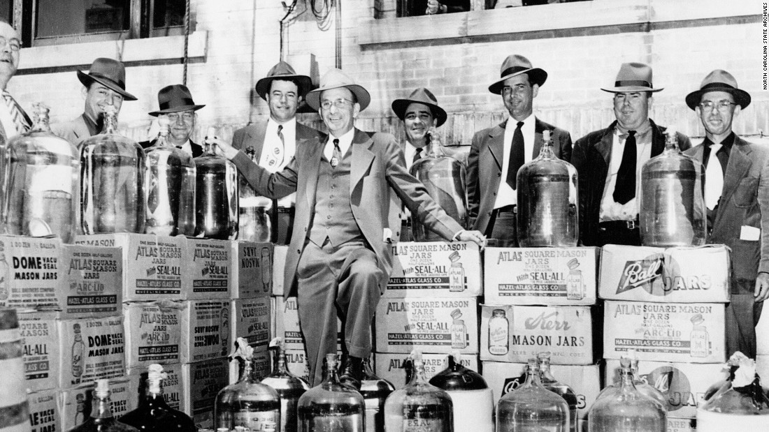 Police pose with confiscated illegal liquor outside Johnson County Courthouse, Smithfield, NC, 1951.