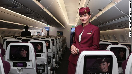 A Qatar Airways flight stewardess poses for a photo.