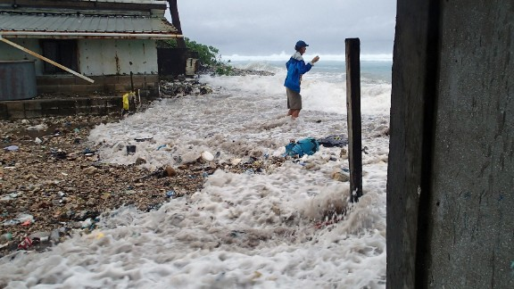 This photo taken on March 3, 2014 shows a resident surrounded by the on-rushing high tide energized by a storm surge that damaged a number of homes across Majuro.   It was the third inundation of the Marshall