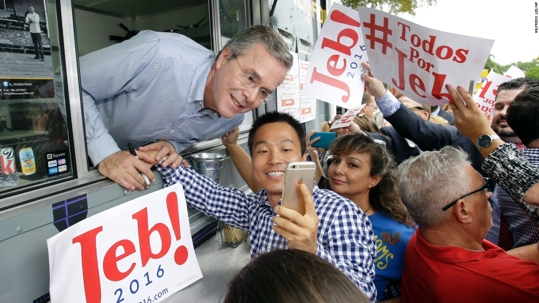 "Former Florida Gov. Jeb Bush poses for a photo as he signed autographs from the window of a food truck Monday, June 15, in Miami. Earlier in the day, Bush <a href=""http://www.cnn.com/2015/06/15/politics/jeb-bush-2016-presidential-announcement/"" target=""_blank"">announced that he would be running for President</a> -- an office held by both his father and his brother."