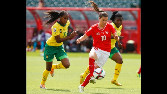 Ramona Bachmann of Switzerland breaks past two Cameroon players.