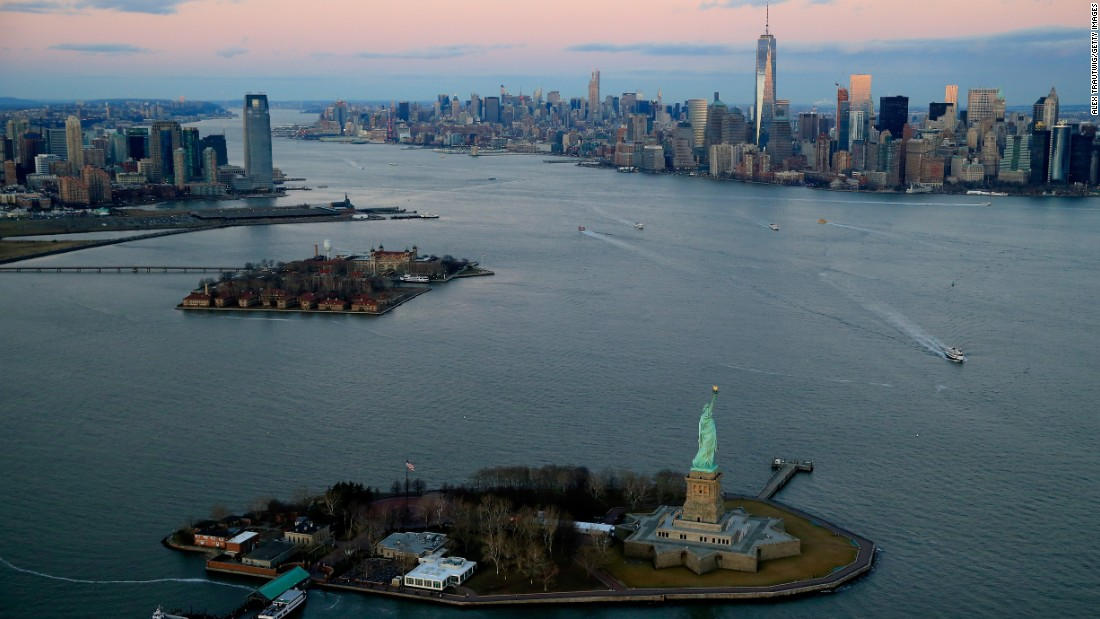 The Statue of Liberty and the One World Trade Center building are seen at sunset in December.