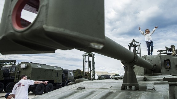 A girl plays on top of field artillery.