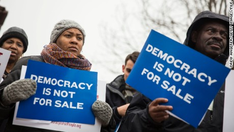 Attendees hold signs as they listen to speakers during a rally calling for an end to corporate money in politics and to mark the fifth anniversary of the Supreme Court's Citizens United decision, at Lafayette Square near the White House, January 21, 2015 in Washington, DC. Wednesday is the fifth anniversary of the landmark ruling, which paved the way for additional campaign money from corporations, unions and other interests and prevented the government from setting limits on corporate political spending. (Photo by Drew Angerer/Getty Images)