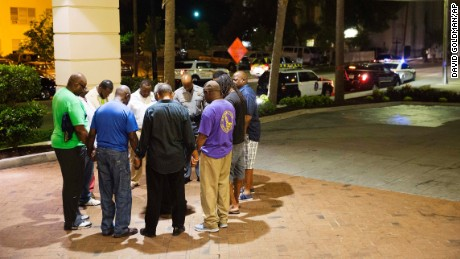 Worshippers gather to pray in a hotel parking lot across the street from the scene of a shooting Wednesday, June 17, in Charleston, S.C.