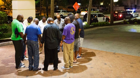 People pray in a hotel parking lot across the street from the scene of the shooting on June 17. Every Wednesday evening, the church holds a Bible study in its basement.