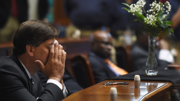 South Carolina state Sen. Vincent Sheheen gets emotional on June 18 as he sits next to the draped desk of Sen. Clementa Pinckney at the statehouse in Columbia, South Carolina. Pinckney was one of the nine people killed in the church shooting.